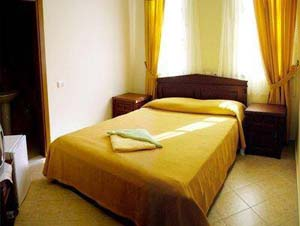 Classic 1 room single with garden view, french bed, private shower shared toilet, and breakfast